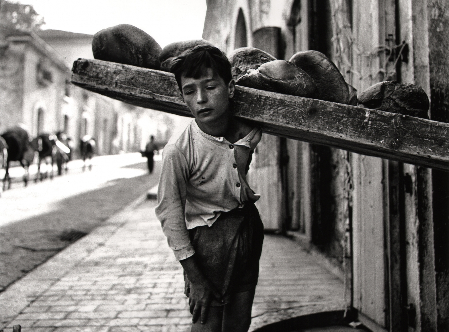 Nino Migliori, Bread Carrier, 1956. A boy carries bread on a wooden plank on his left shoulder.