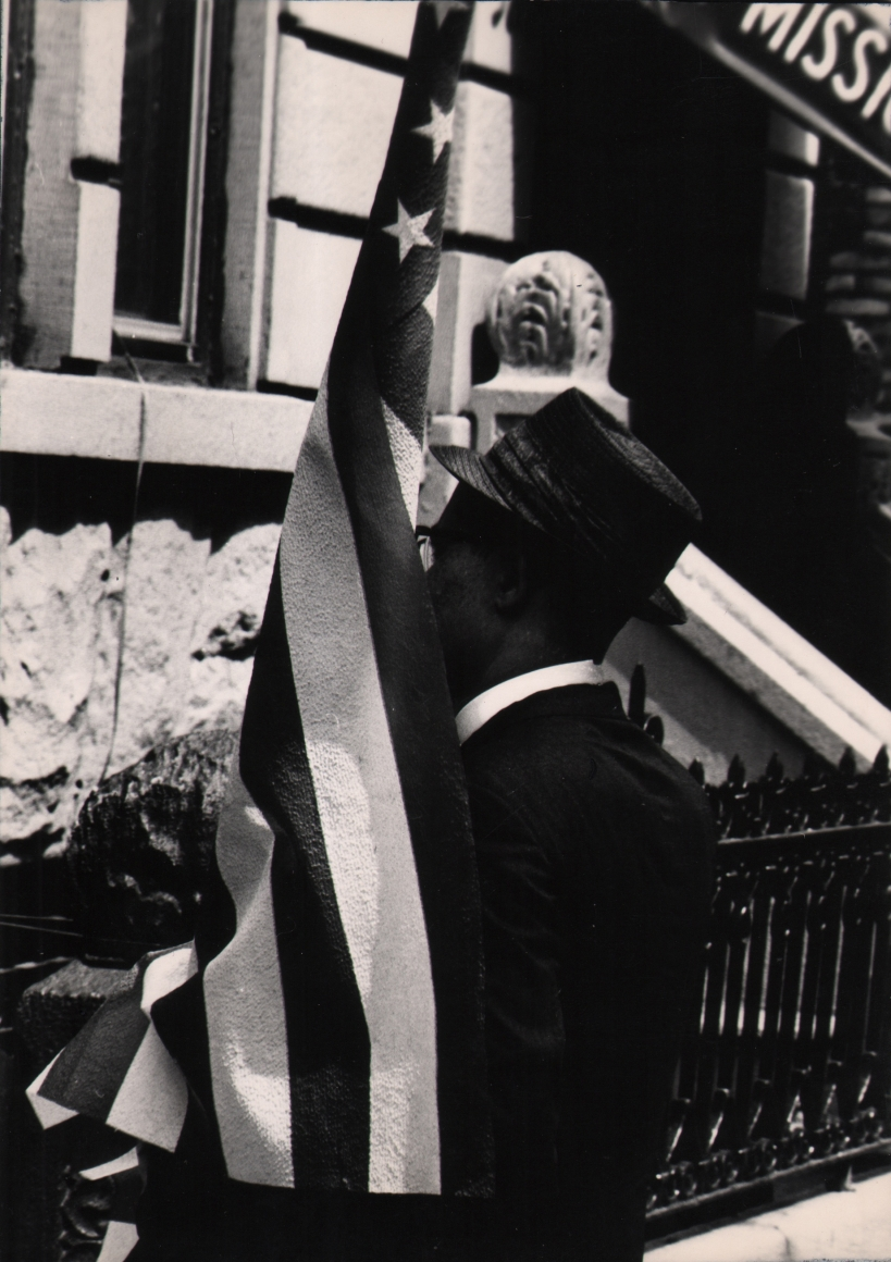 22. Shawn Walker, Untitled, c. 1965. Man in a jacket and hat carries an American flag, facing away from the photographer.