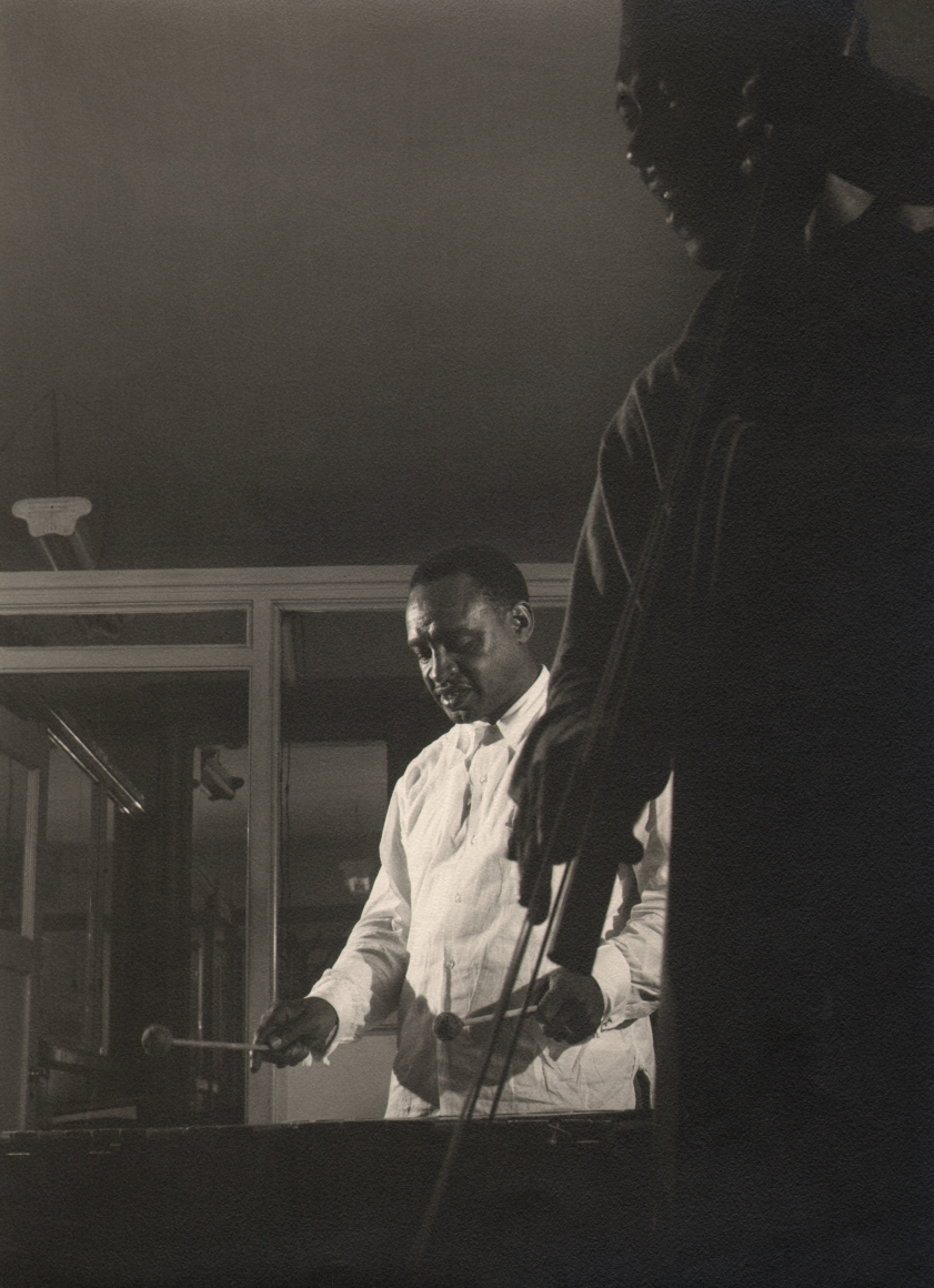 Bob Willoughby, Lionel Hampton on Vibes, 1956. Subject looks down while striking his instrument with another musician in the foreground.