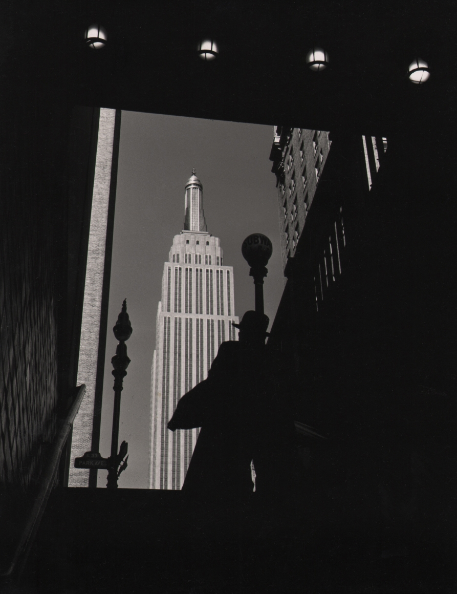 19. John C. Hatlem, Empire State Building, c. 1935. View from the bottom of subway entrance stairs, looking out and up towards the Empire State Building. A figure in a hat stands on the stairs and is silhouetted against the building.