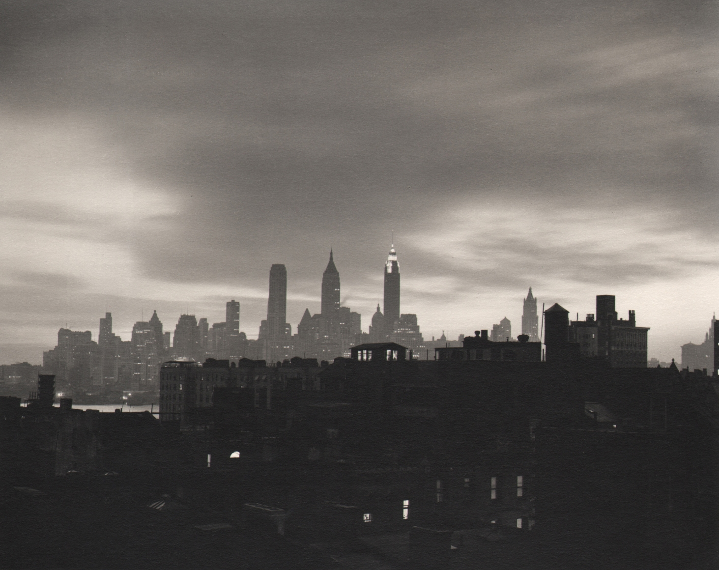 35. John C. Hatlem, New York City Skyline, c. 1935. Dark, mostly silhouetted view of the city from across a river. Dark buildings in the foreground. The Empire State is in the center background against a cloudy sky.
