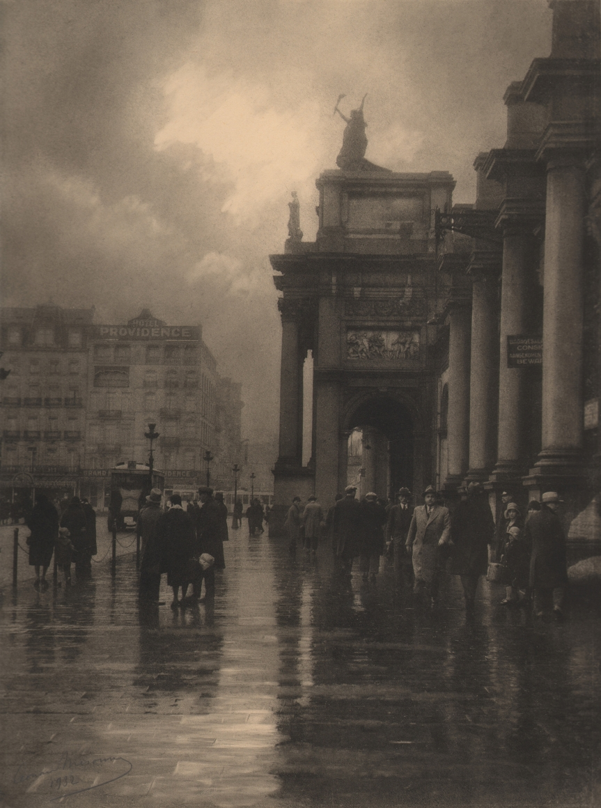 05. Léonard Misonne, Après la pluie, 1932. Crowded, wet sidewalk in front of an ornate, columned building against a cloudy sky. Sepia-toned print.