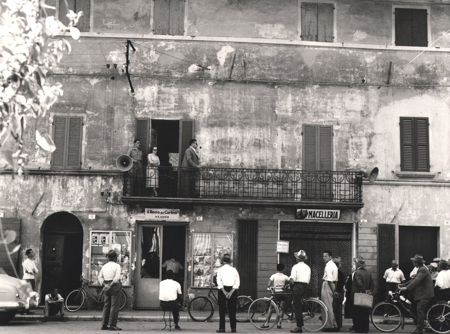 Nino Migliori, Meeting in the Province, 1957. People gather in the street as a man speaks into a microphone from a balcony.