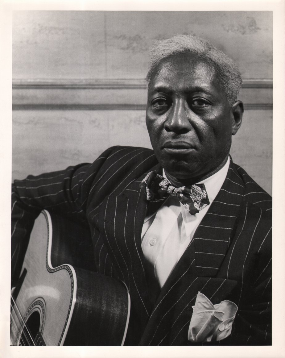 Gordon Coster, Leadbelly, c. 1940. Subject holds a guitar and looks into the camera with a serious expression.