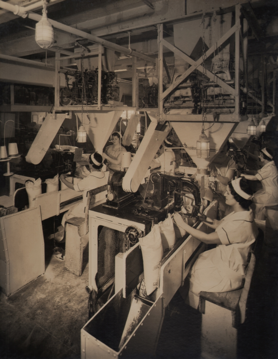 Harold Haliday Costain, Long Island City Plant, 1935. Rows of women operate machinery.