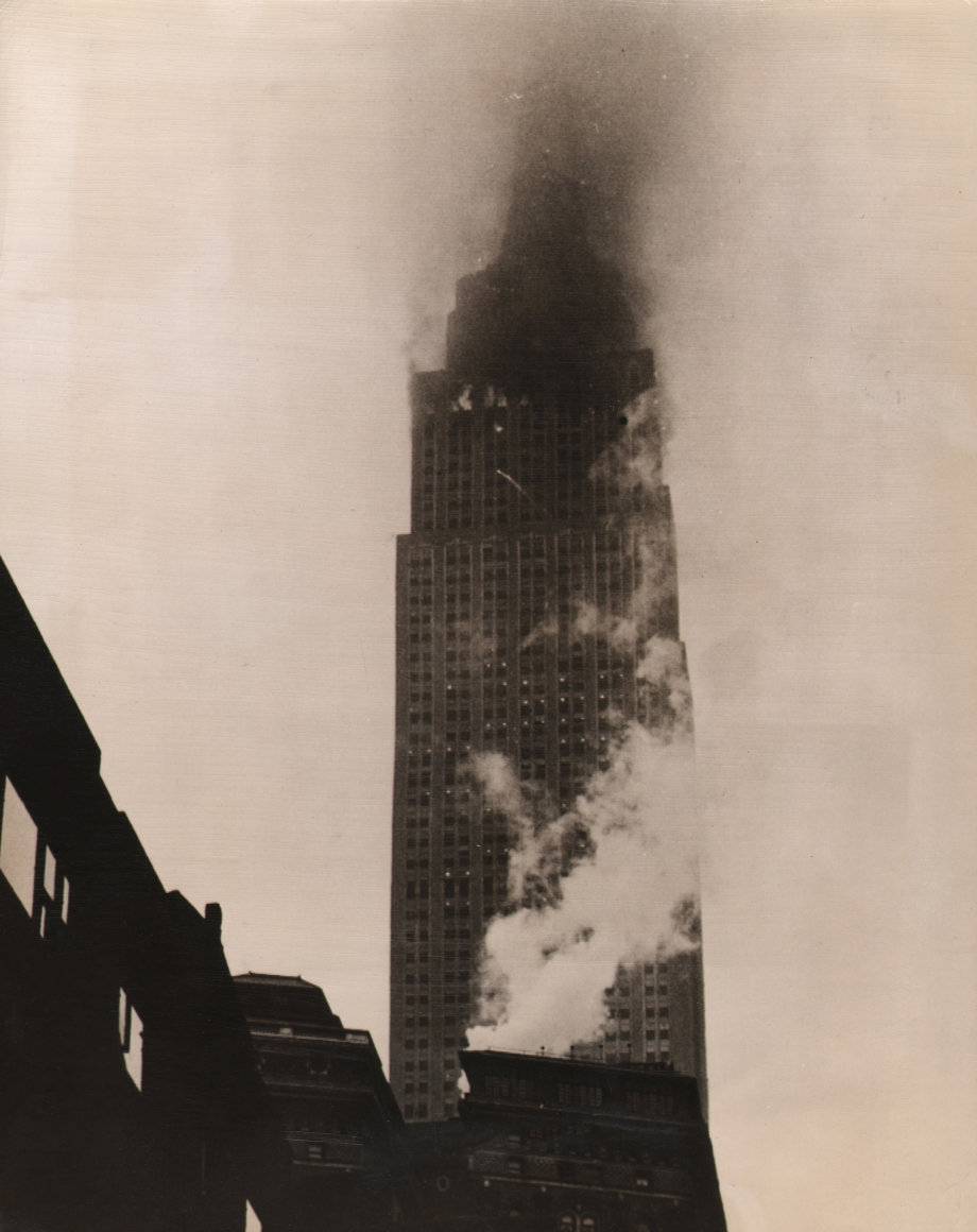 02. Anonymous, Empire State Afire After Plane Crash, 1945. Street view of a skyscraper with smoke emitting from the upper floors.