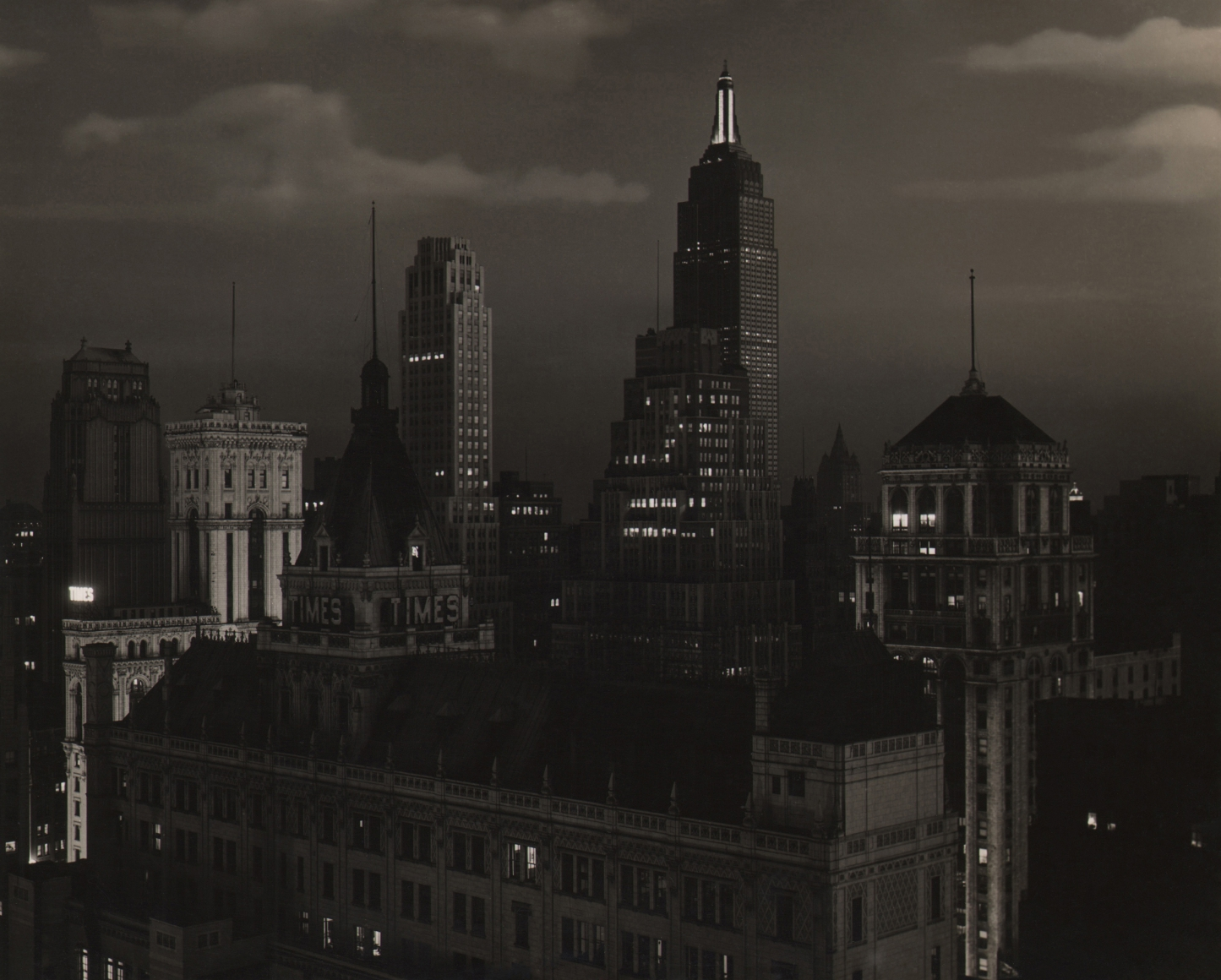 Paul J. Woolf, Times Building Looking South, c. 1935. Night time cityscape with partly cloudy skies.