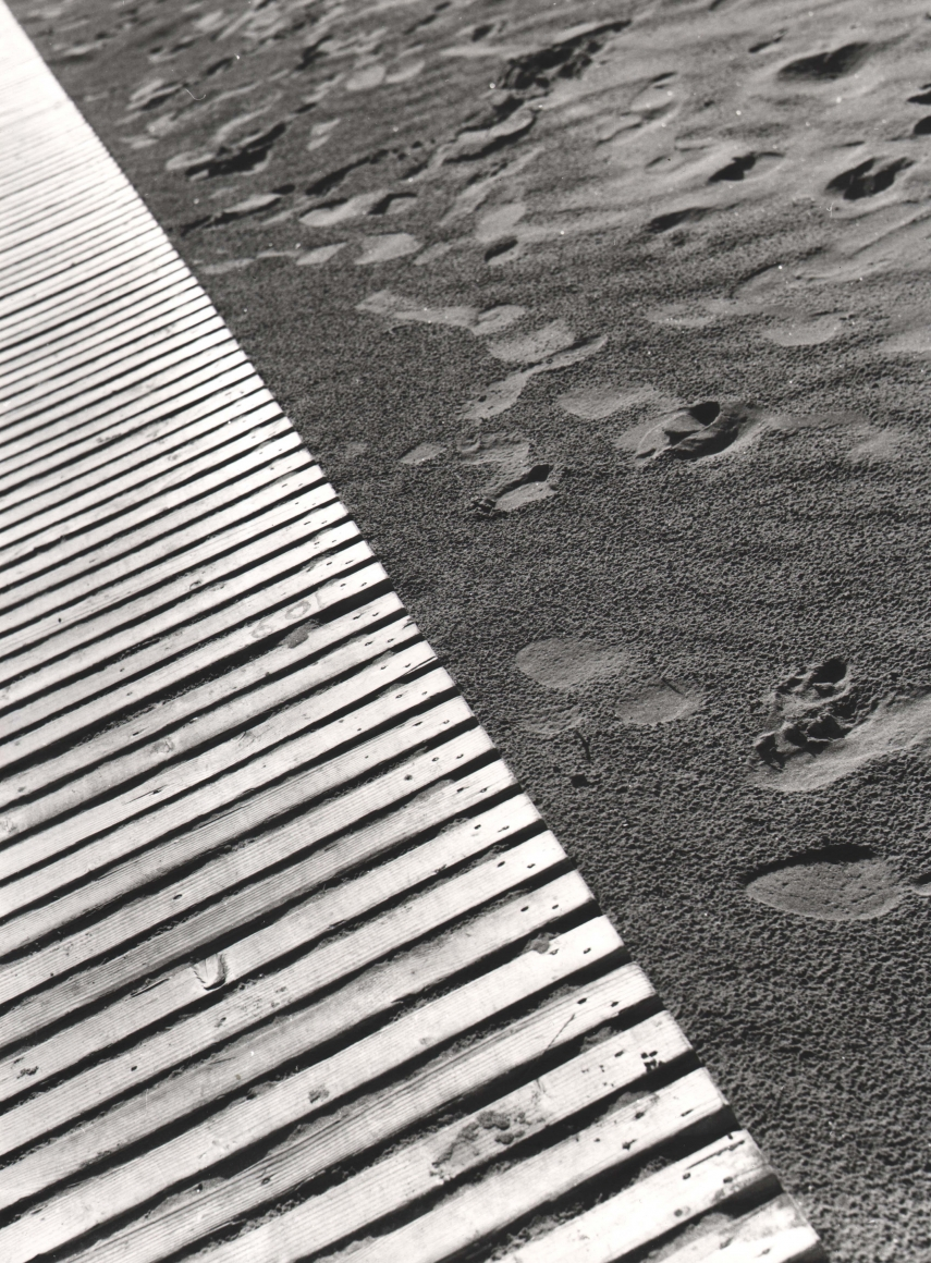 Nino Migliori, Untitled, 1951. Frame is diagonally divided; one half is a wooden dock, the other footprints in the sand.