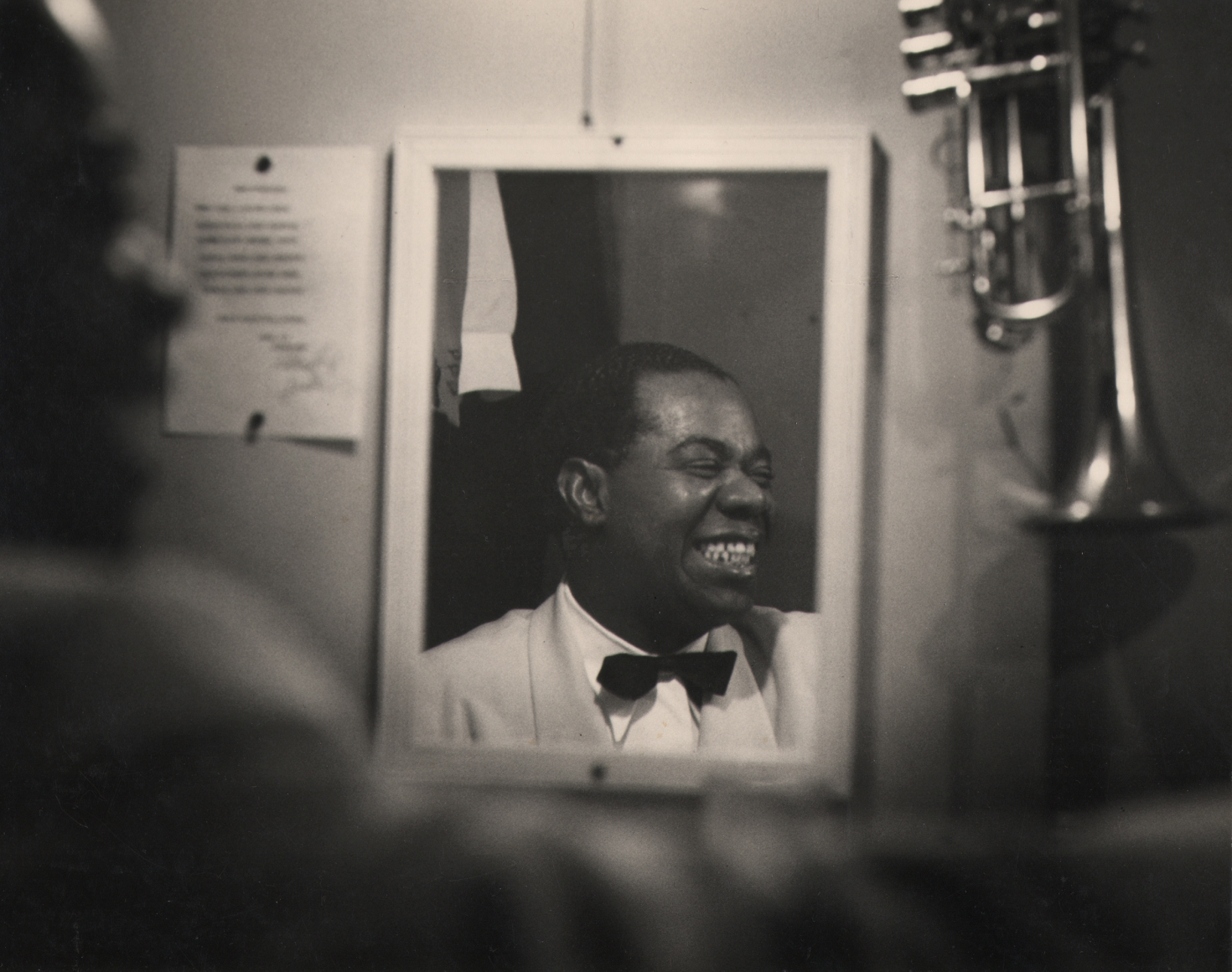 Bob Willoughby, Louis Armstrong, 1950. Subject is seen smiling in a mirror reflection, head turned to the right.