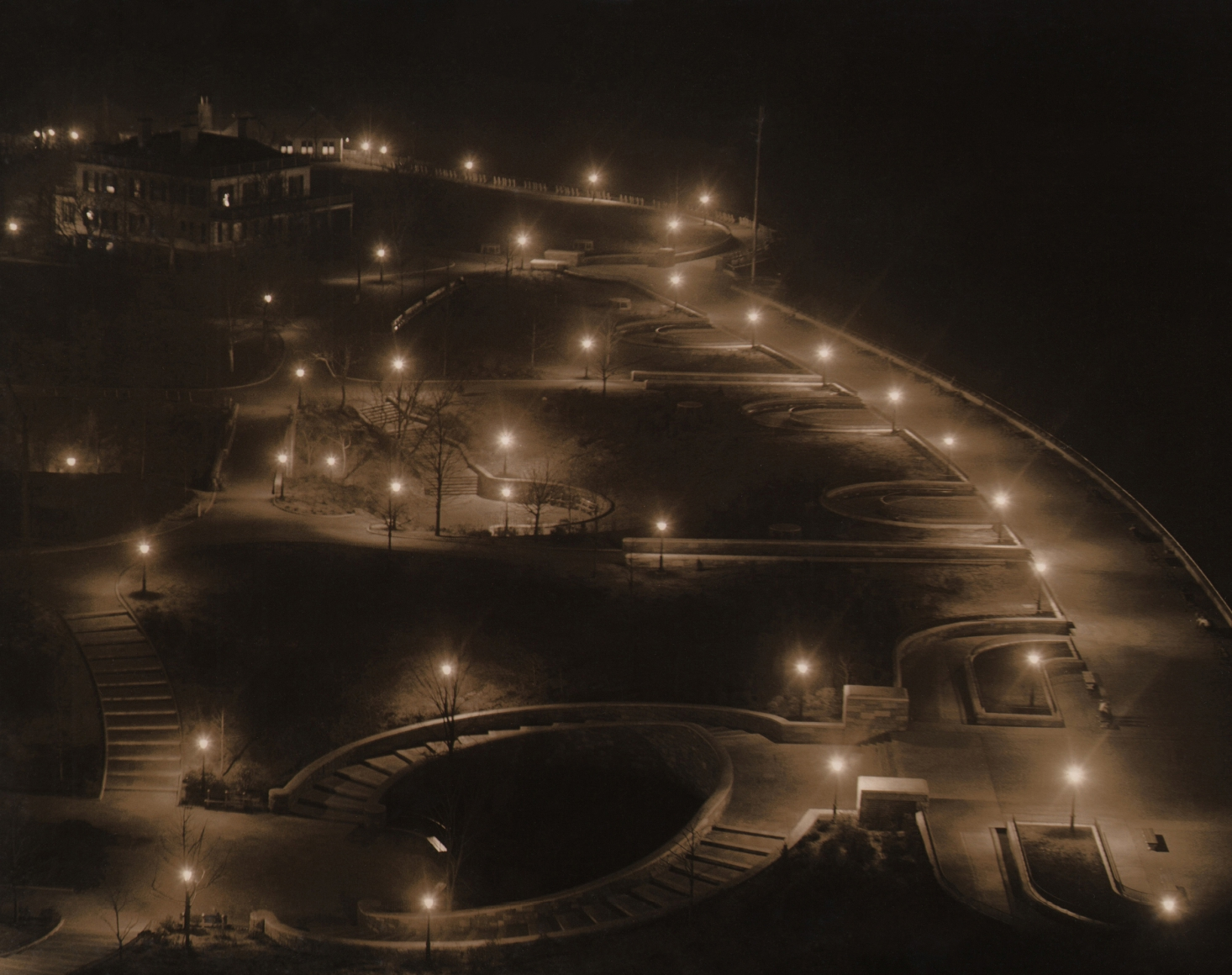 Paul J. Woolf, Carl Schurz Park, c. 1935. Night time view of a park with street lights illuminating various walking paths and stairways.