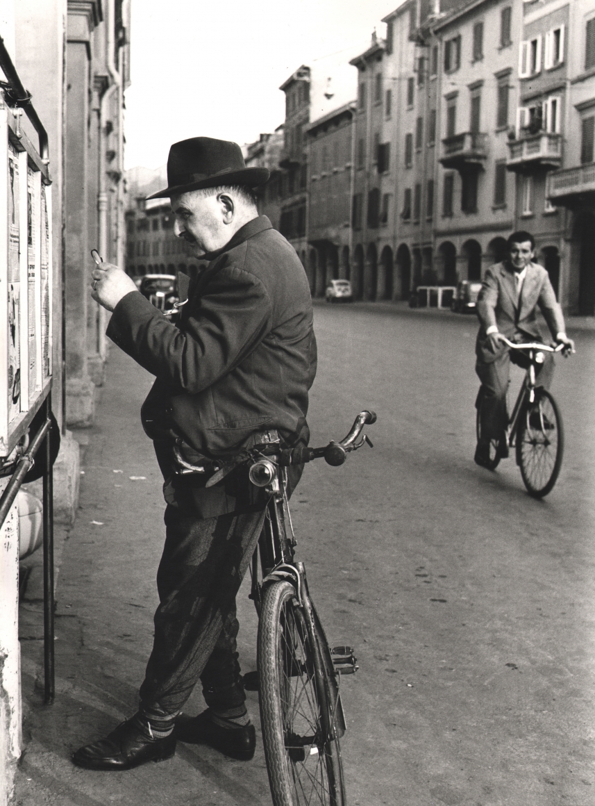 Nino Migliori, People of Emilia, 1950. Street scene featuring a man leaning on his bicycle in the foreground while another man rides a bicycle in the background.