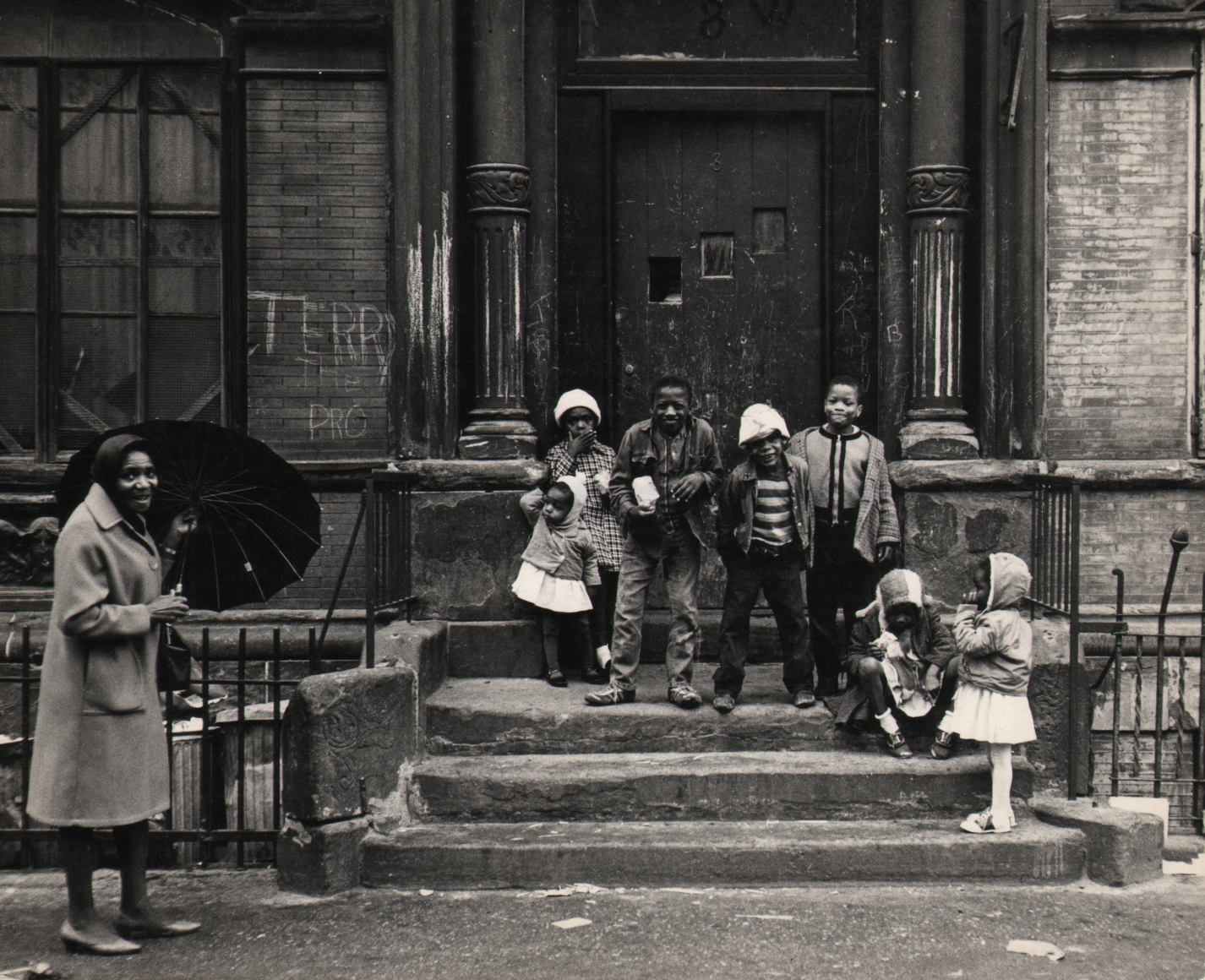 31. Beuford Smith, Harlem Children, Easter Sunday, 1965. Seven children lined up on a stoop; a smiling woman holding an umbrella stands in the lower left of the frame.