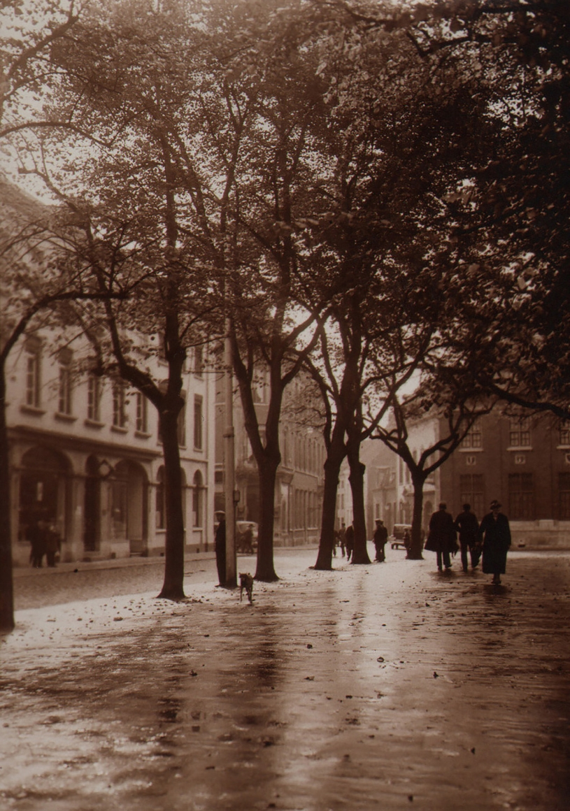 22. Léonard Misonne, Untitled, c. 1930. Silhouettes in the midground of a tree-lined street scene with wet pavement. Sepia-toned print.