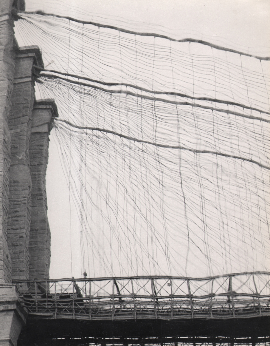 27. David Attie, Brooklyn Bridge, c. 1958. Distorted image of a portion of the Brooklyn Bridge from a low perspective. Most of the frame is filled with distorted, wavy cables.