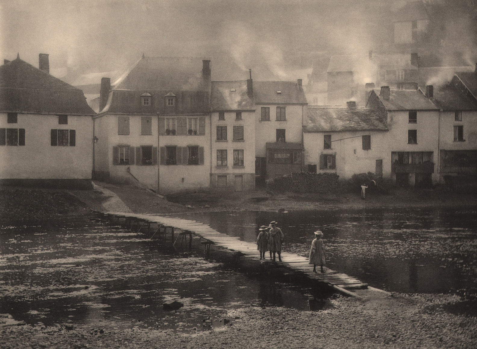 15. Léonard Misonne, On alume le jeux, 1924. Three young girls walk across a small body of water on a wooden dock. Waterside homes with smoke rising above them in the background. Sepia-toned print.