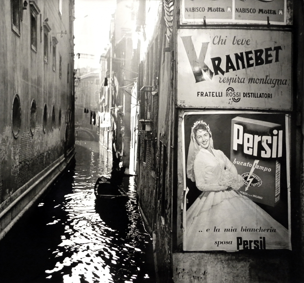Nino Migliori, Venice, 1958. A canal with one boat running between buildings. Advertisements on the right.