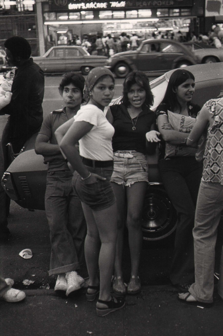 11. Anthony Barboza, Coney Island, NY, 1970s. A group of young people socializing by a parked car. The central figure looks to the camera in a white t-shirt with hands in her back shorts pockets.