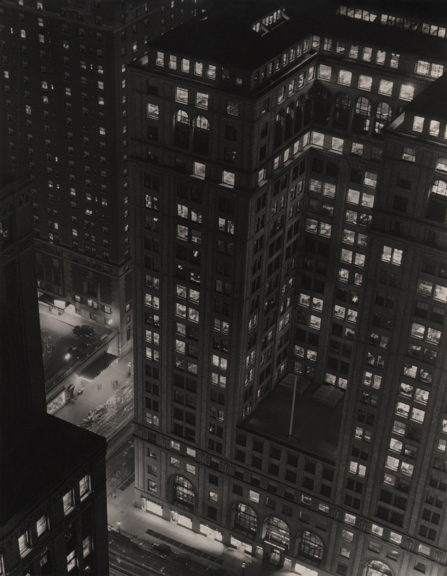 Paul J. Woolf, Grand Central, c. 1935. Night time view looking down towards two intersecting streets and tall buildings rising above them.