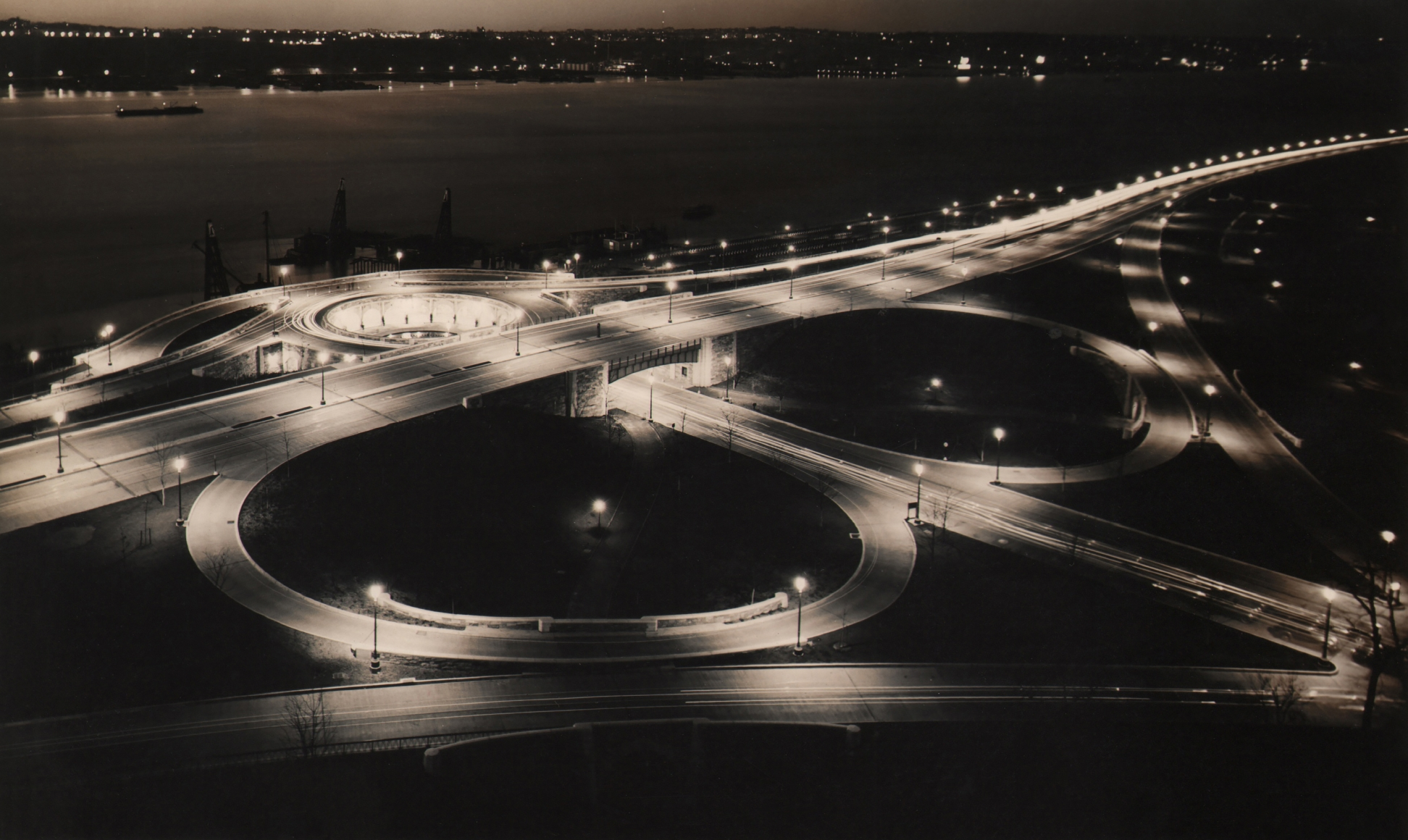Paul J. Woolf, 86th Street Clover Leaf at Night, c. 1935. Night time view of riverside street with circular on- and off-ramps.