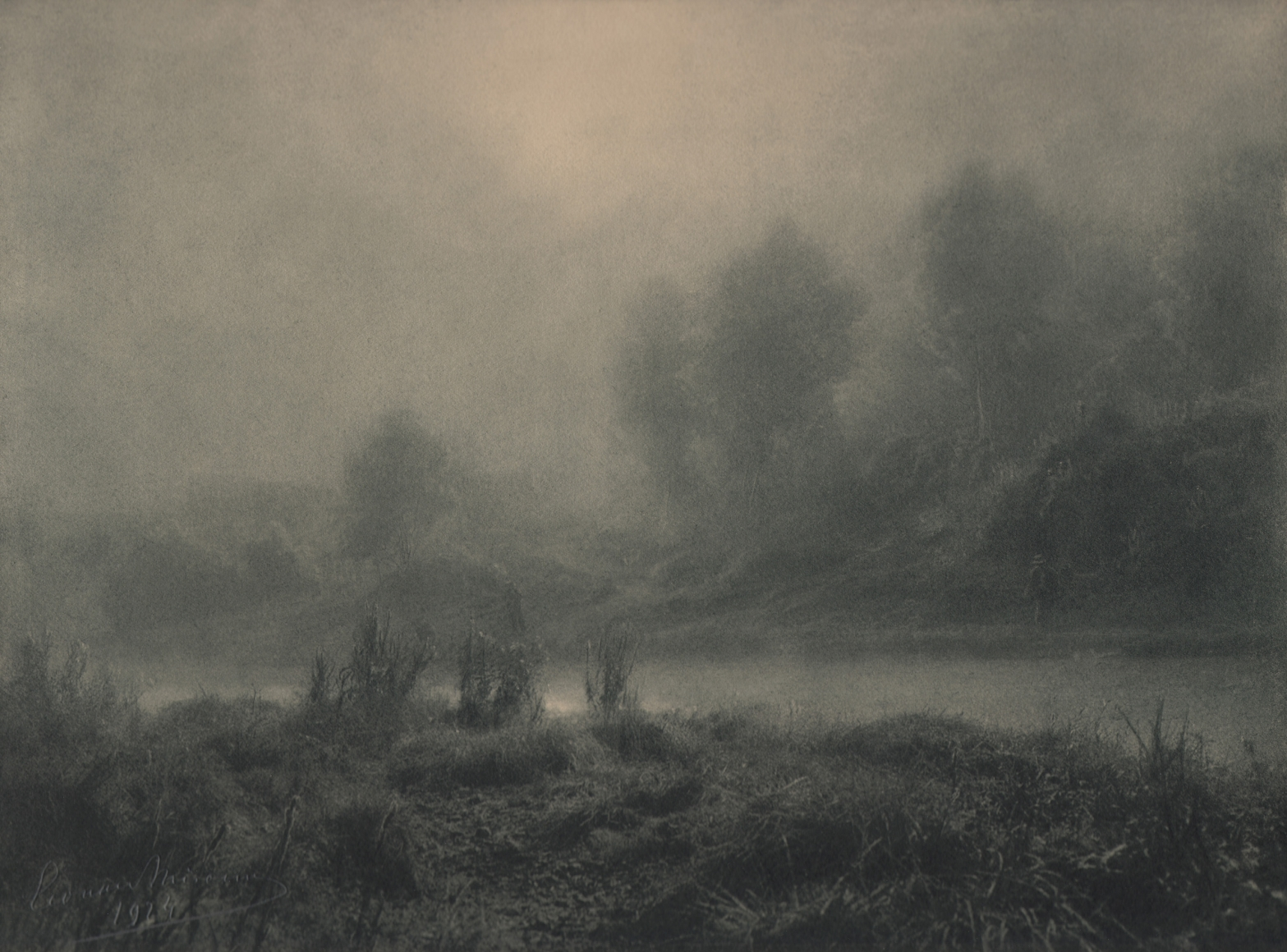 13. Léonard Misonne, Lever de soleil, c. 1924. Hazy sunrise alongside a river with brush and trees on either side. Gray/green-toned print.
