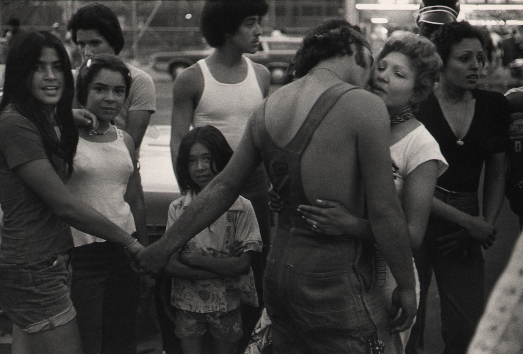 12. Anthony Barboza, Coney Island, NY, 1970s. Crowd of people. Central figure is a man in overalls with back to the camera. He holds one woman's hand while embracing another.