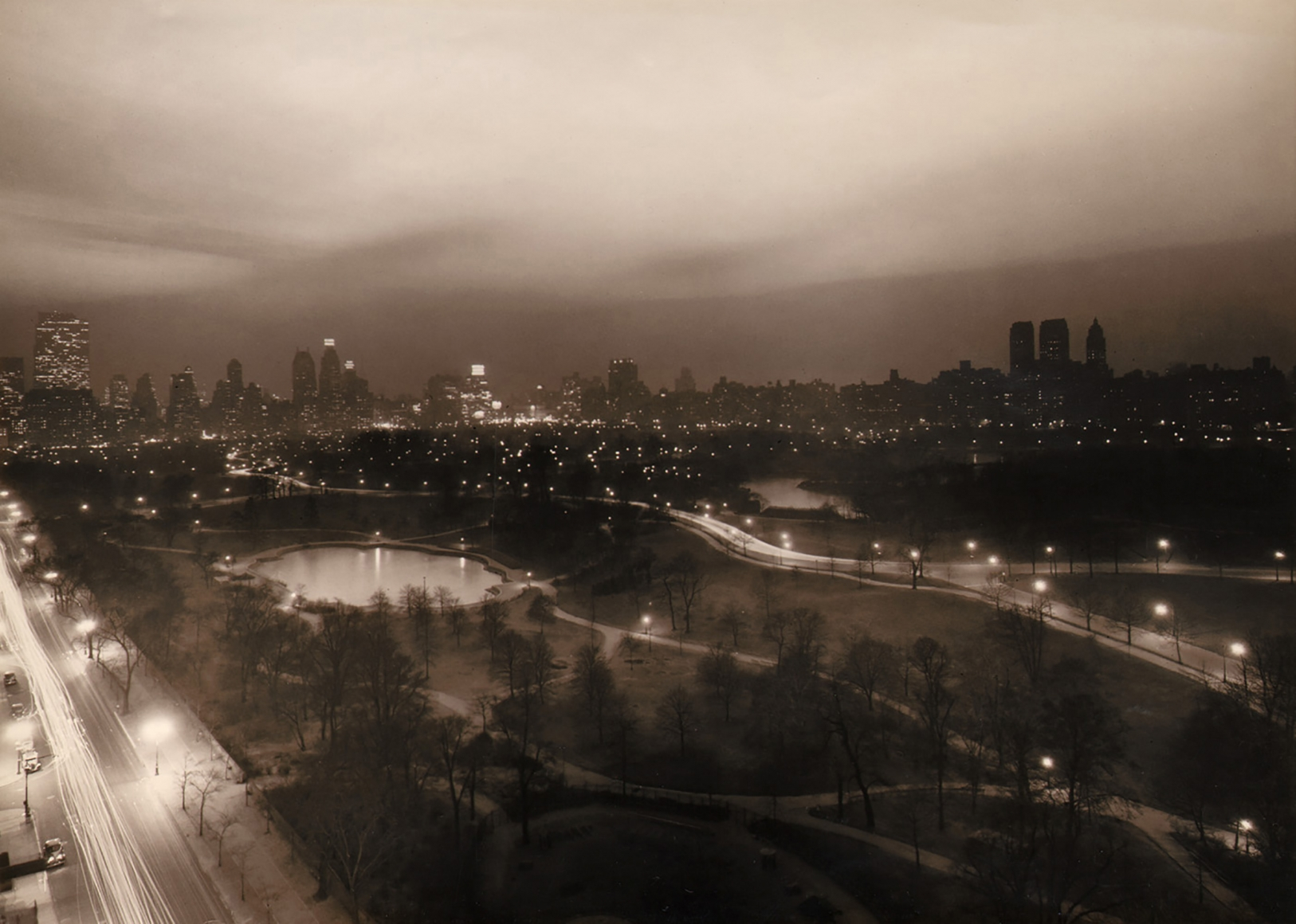 Paul J. Woolf, Central Park Looking South, c. 1936. Night time cityscape with the park filling the lower half of the frame, a street running up the lower left. Tall buildings across the center of the frame and an overcast sky above.