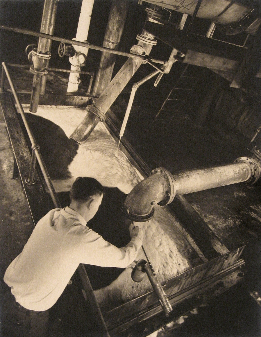 Harold Haliday Costain, Edgewater, NJ Sugar Refinery, 1935. A man leans over a tub as a pipe dispenses sugar into it.