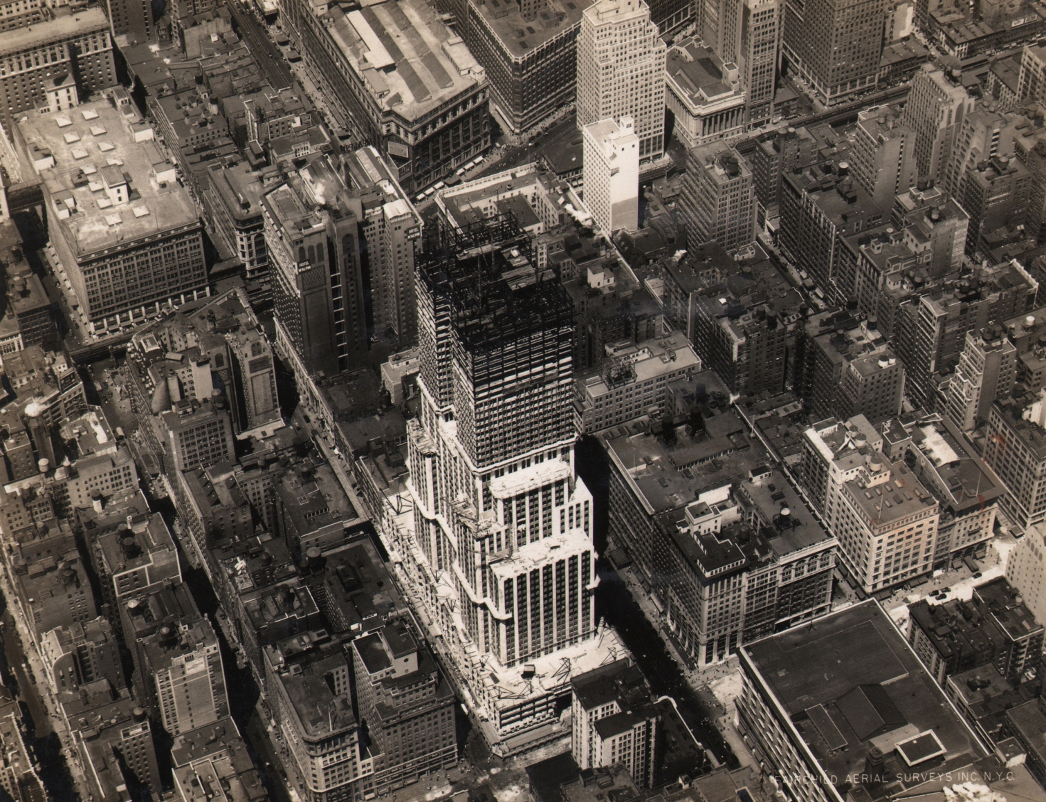 22. Fairchild Aerial Surveys, Empire State Building Construction, West 34th Street, New York City, 1930. Aerial view of the in-progress Empire State Building, built up to about half its total height.