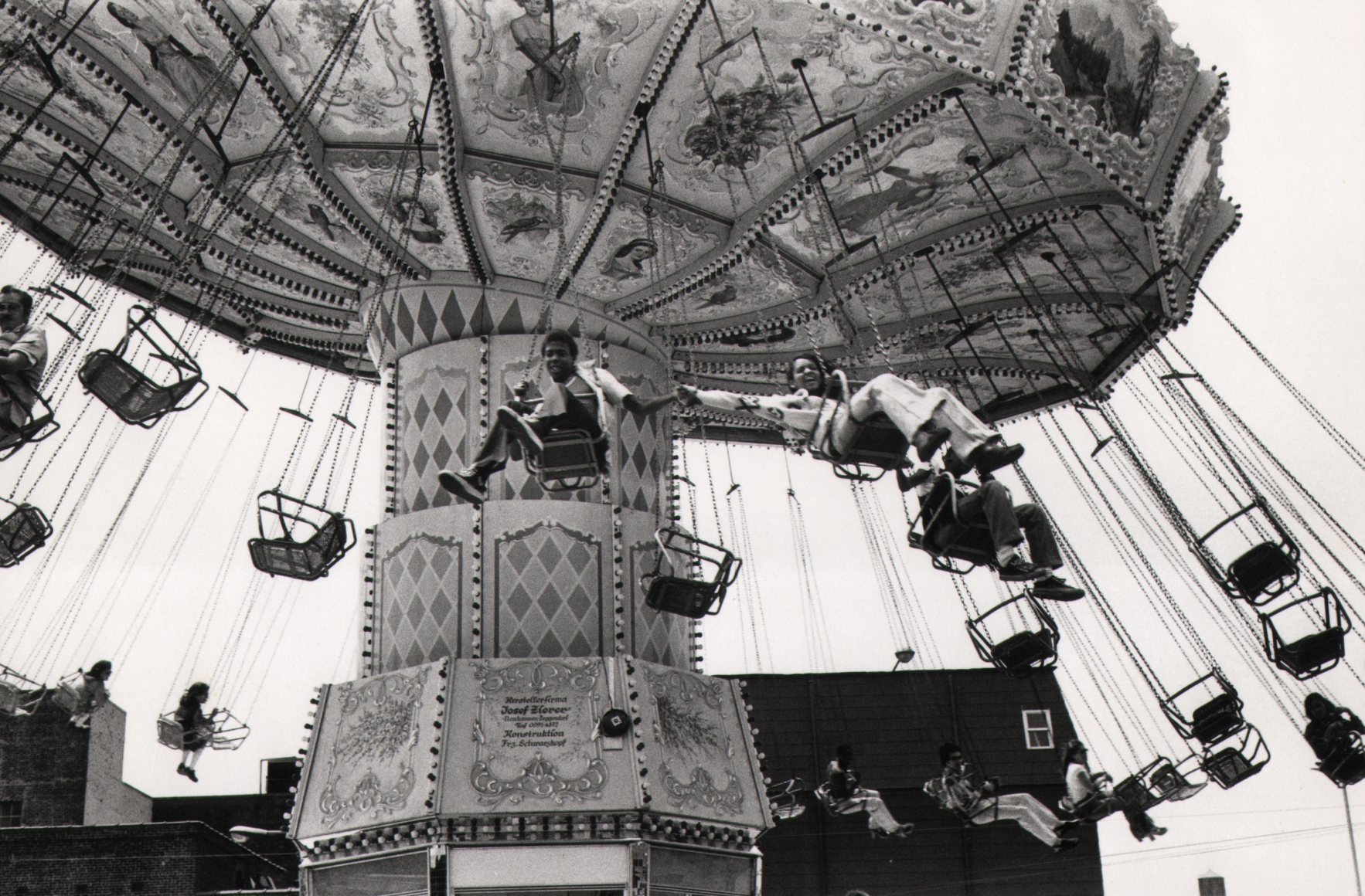 18. Anthony Barboza, Coney Island, 1970s. A carnival swing in motion, photographed from below. The two closest riders hold hands.