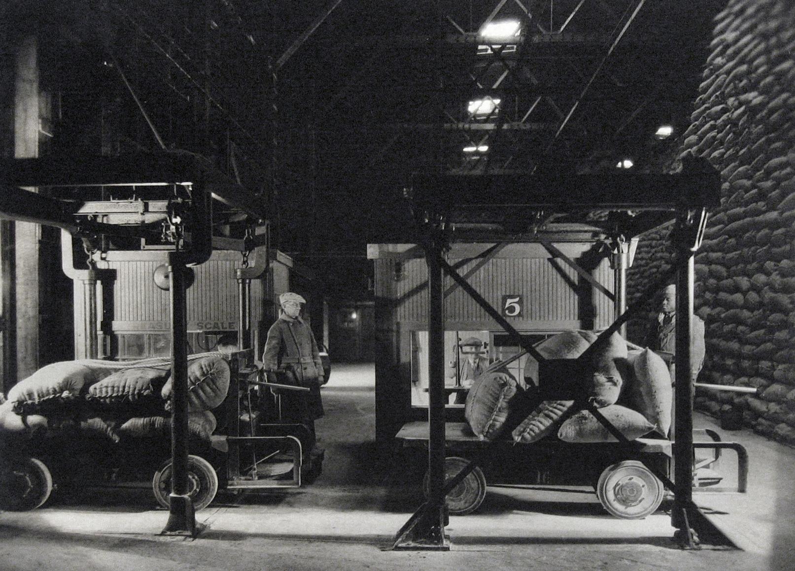 Harold Haliday Costain, Edgewater, NJ Sugar Refinery, 1935. Two men load sugar sacks onto carts.