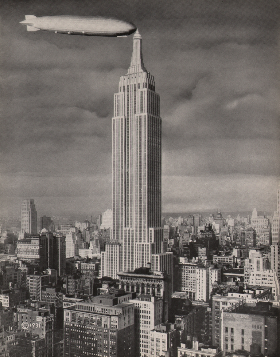 """18. Panorama Studio, Empire State Building & Dirigible """"Los Angeles,"""" 1931. Head-on view of the Empire State Building against a cloudy sky. The nose of a dirigible meets the building's tower on the left."""