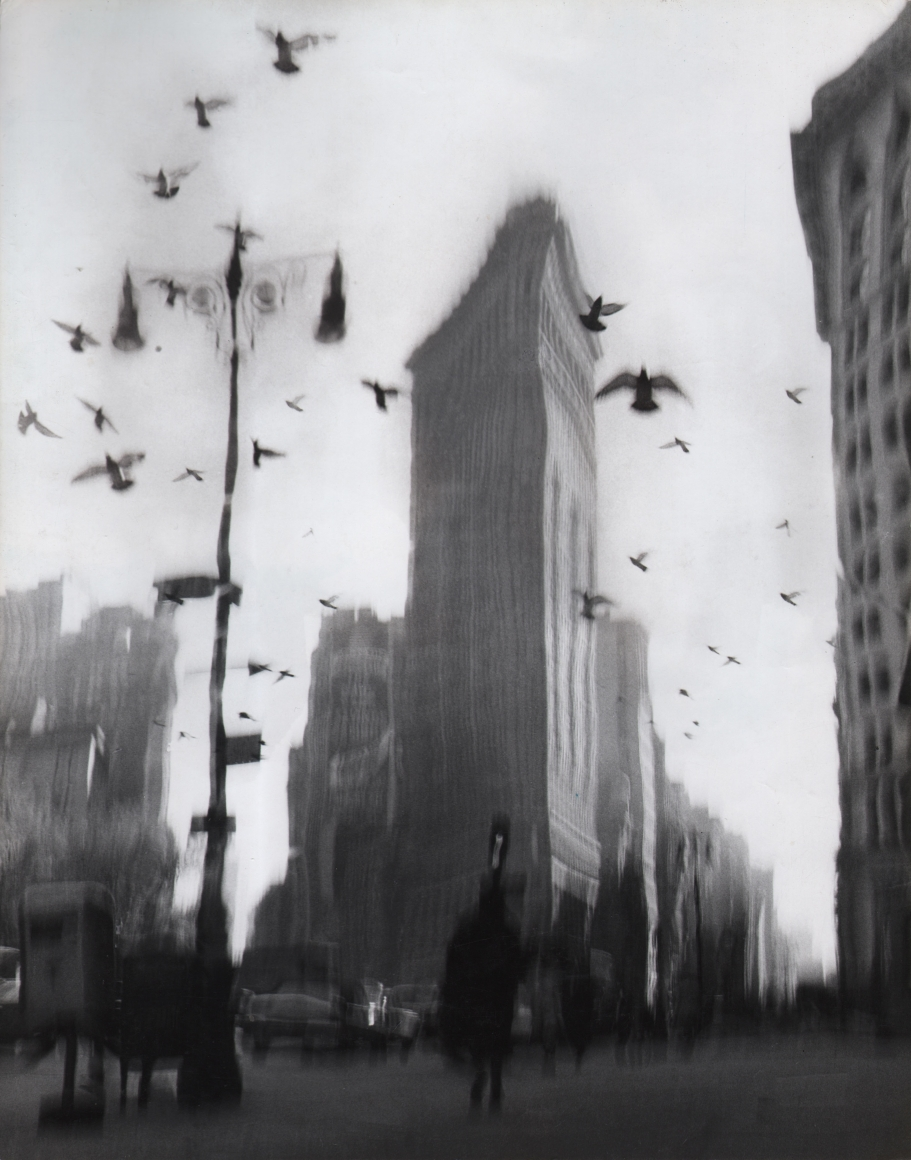26. David Attie, Flatiron Building, c. 1958. Blurred/distorted photo of a triangular building against a gray sky. Various figures and cars can be seen in the lower third of the print, below a number of birds taking flight.