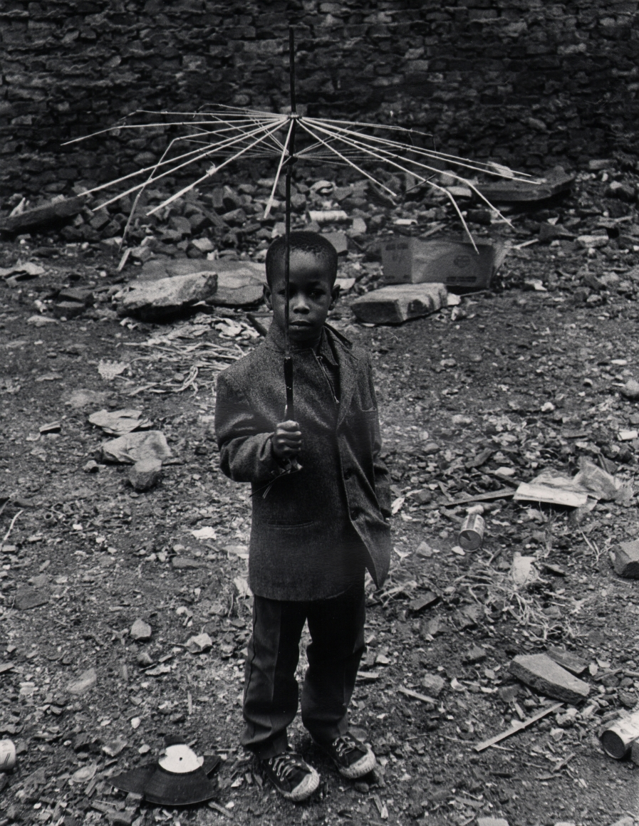 36. Beuford Smith, Boy with Umbrella, 1973. A young boy holds a broken umbrella, with only wires remaining, above his head.