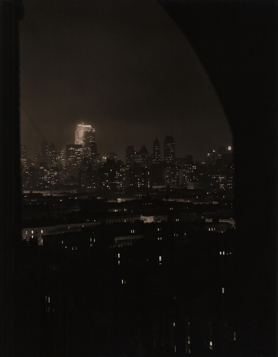 Paul J. Woolf, Rockefeller Center Looking South, c. 1935. Night time cityscape photographed from beneath a dark arch.