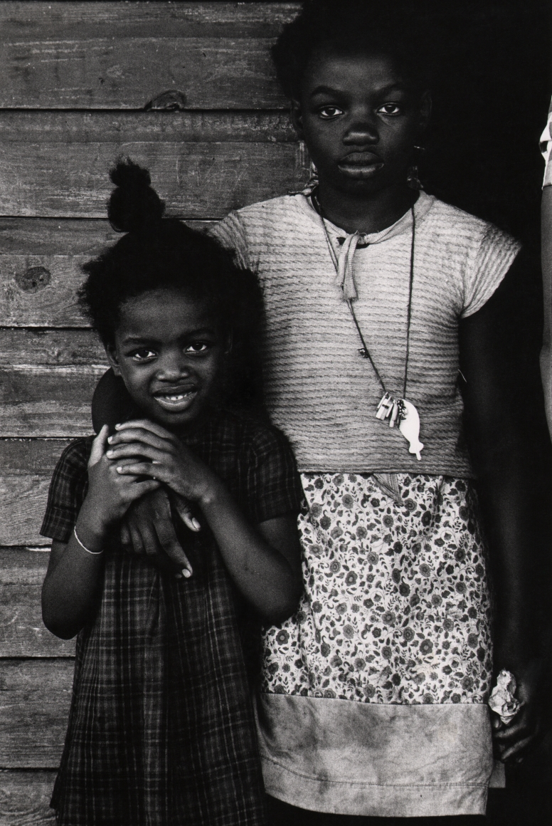 14. Anthony Barboza, Jacksonville, Florida, 1960s. Two young girls stand side by side, the taller one has her right arm around the other. Both look to the camera; the smaller child is smiling.