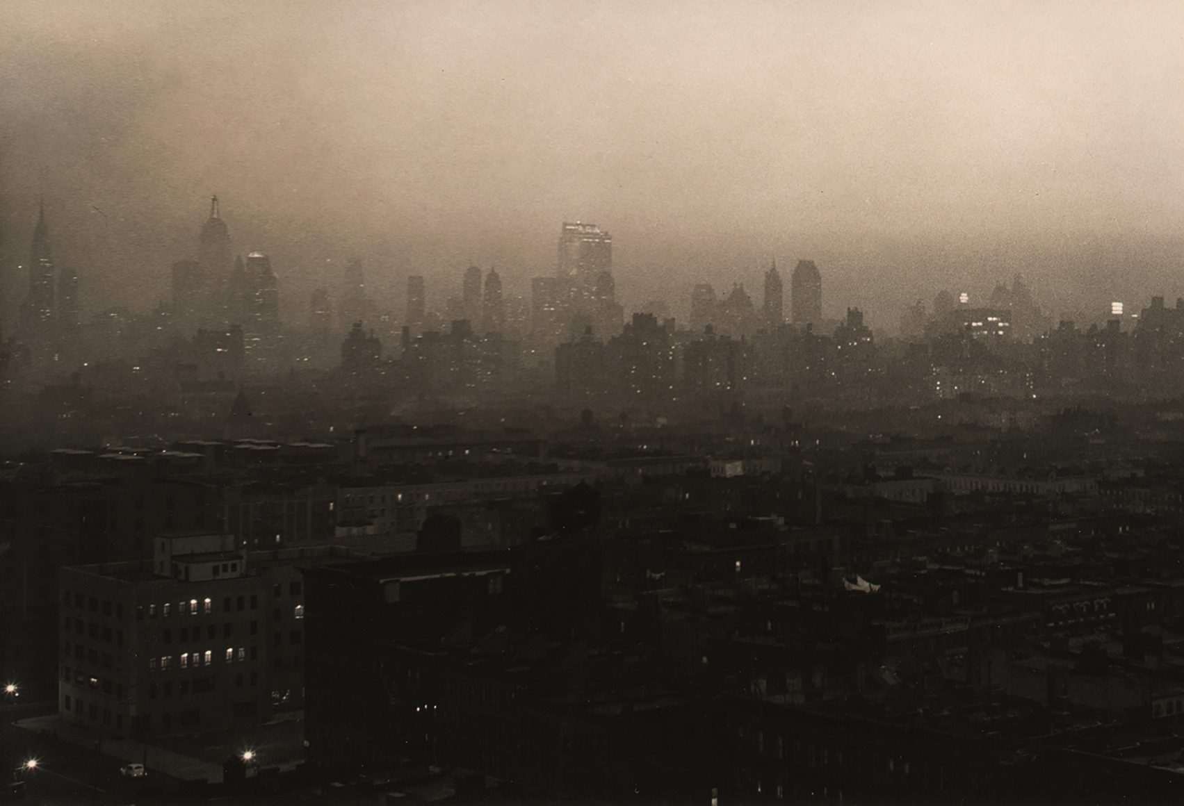 Paul J. Woolf, New York Skyline Evening Haze, c. 1936. Dark and hazy cityscape with skyscrapers in the distance silhouetted across the frame.