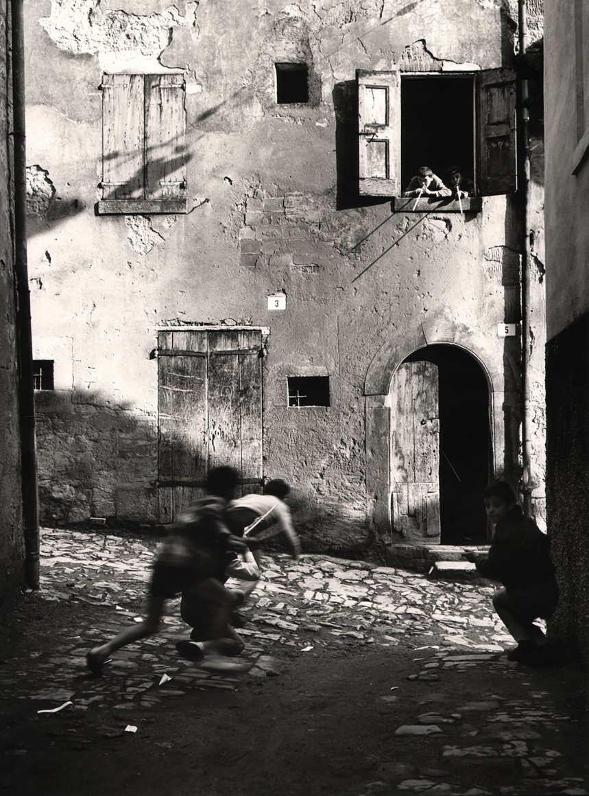 Nino Migliori, The Street Kids, 1955. Five boys play with peashooters in an alley. Three are on the street, two are leaning out a second story window.