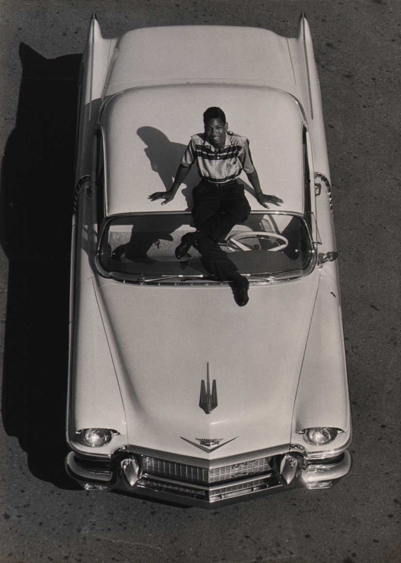 Flip Schulke, Little Willie John's 'Fever,' 1956. Subject is photographed from above sitting on the hood of a car, smiling up at the camera.