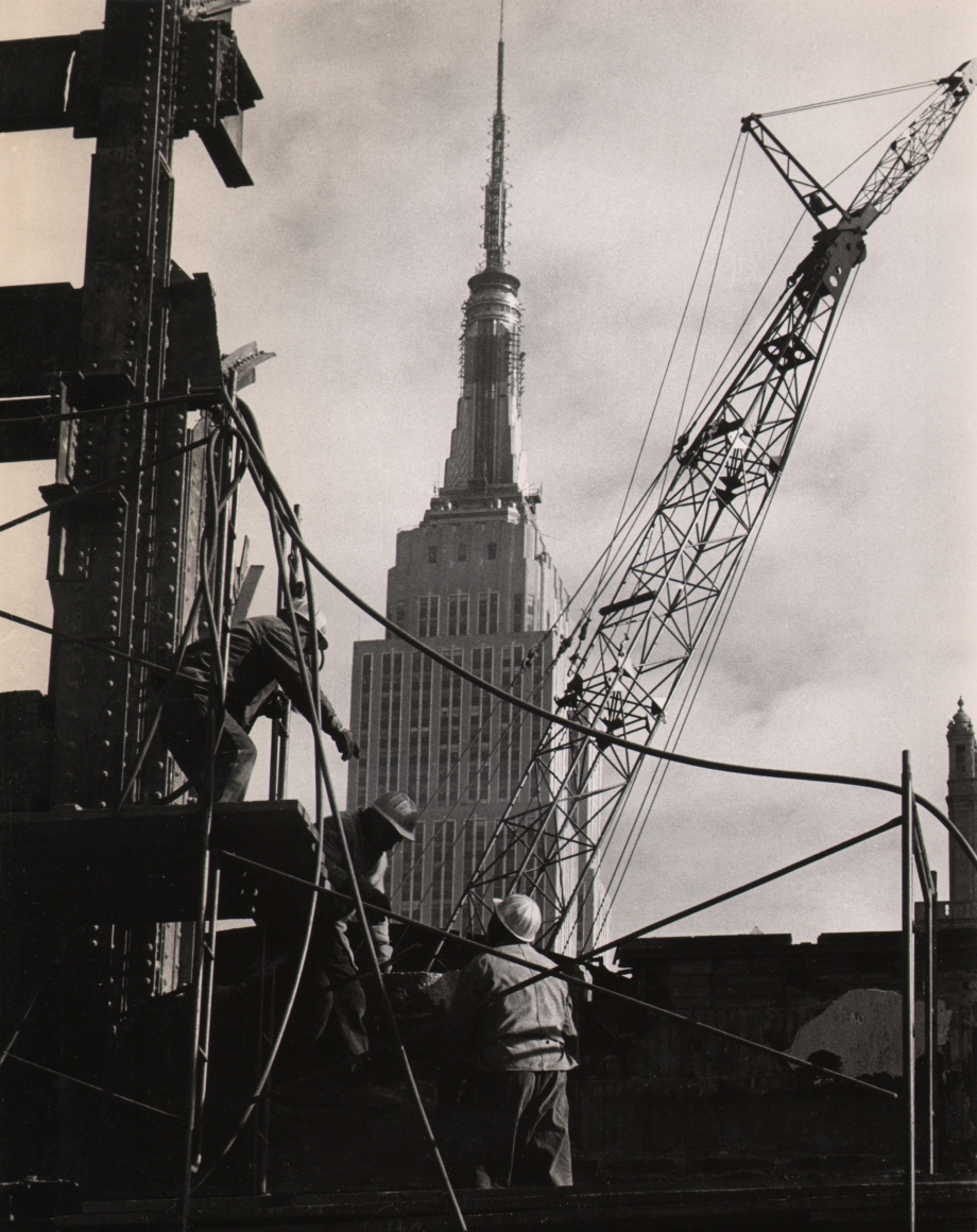 13. UPI Photo, Demolishing remains of Pennsylvania Station, 1966. Workmen in the foreground amongst metal support structures and a crane. The top half of the Empire State Building is visible in the center background against a cloudy sky.