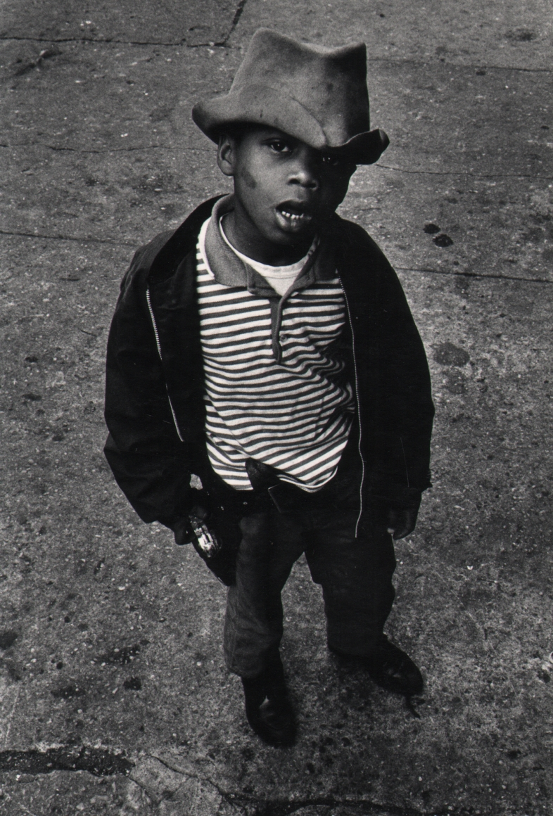 24. Shawn Walker, Harlem, 117th Street, 1960s. A young boy in a hat and striped shirt and dark jacket looks up to the photographer with mouth open.