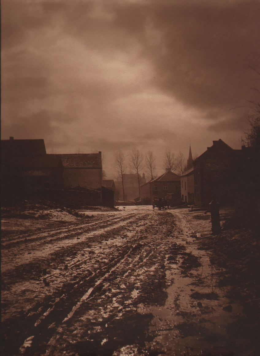 24. Léonard Misonne, Untitled, c. 1930. Muddy street, buildings in the midground, and cloudy sky above. Deep sepia-toned print.
