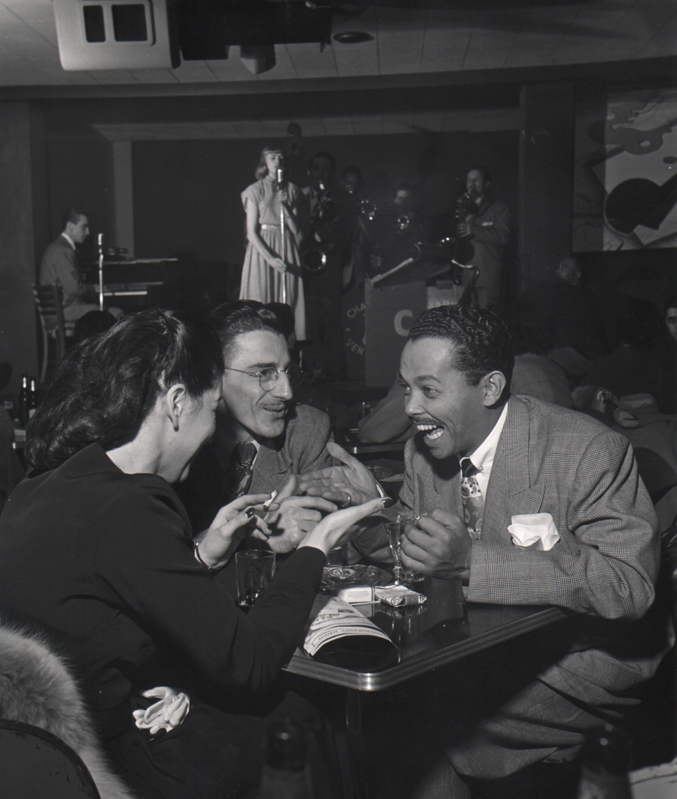 Wayne F. Miller, Billy Eckstine, 1948. Subject is seated, smiling, at a club table with two other figures. A woman sings on stage in the background.