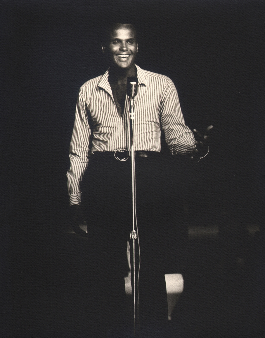 Flip Schulke, Harry Belafonte, c. 1960. Subject stands on stage behind a microphone, smiling out towards his audience and the camera.