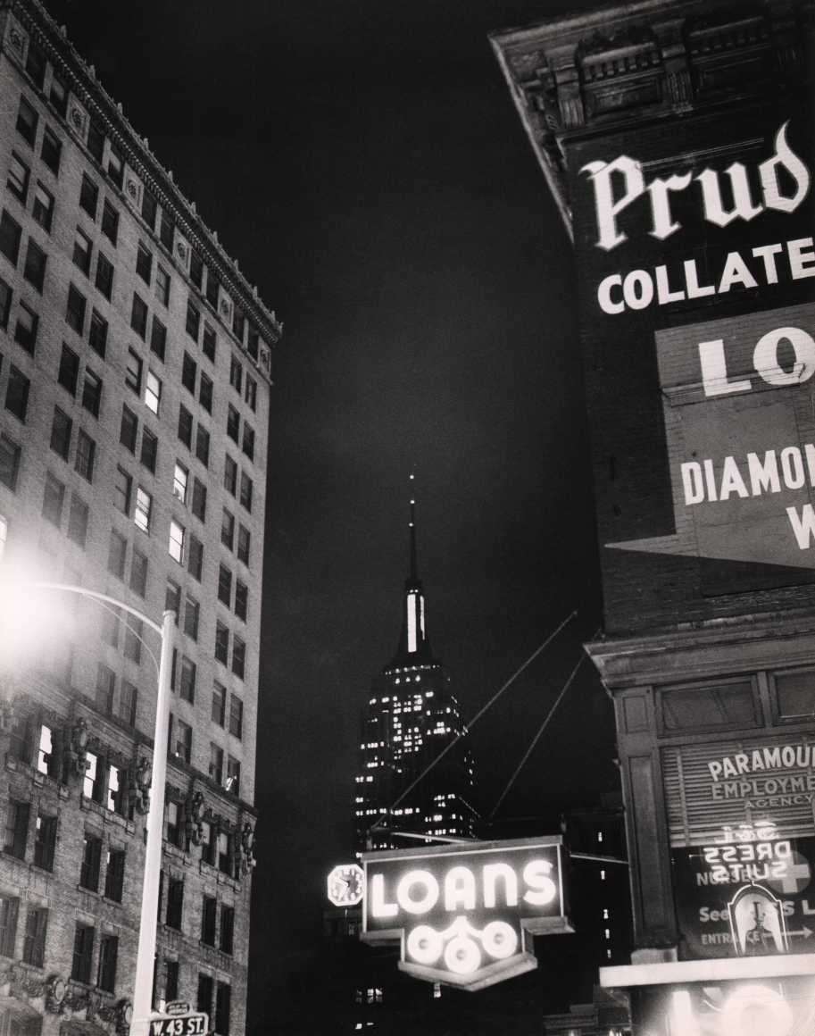 """34. Weegee, West 43rd Street, c. 1950. Nighttime street view facing the Empire State Building pictured between an unmarked building on the left and a """"Loans"""" business with a neon sign on the right."""