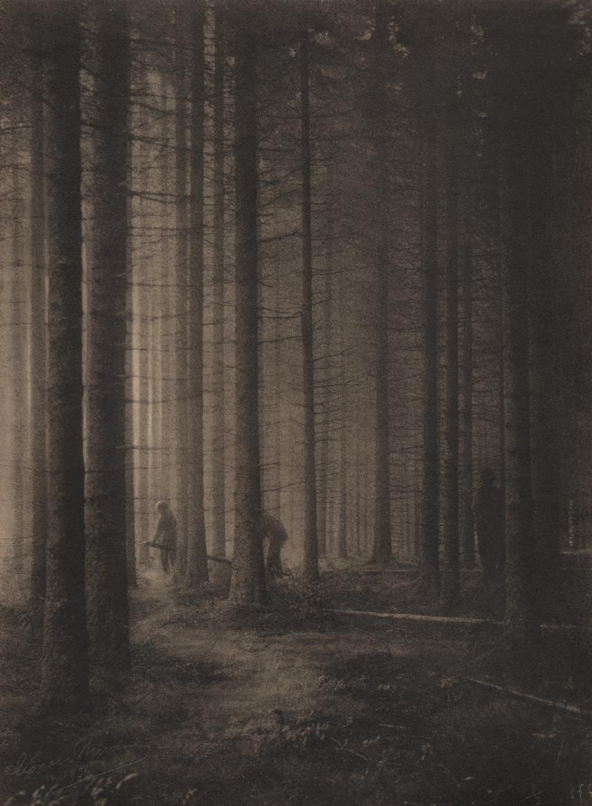 01. Léonard Misonne, Les bucherons, c. 1934. Three lumberjacks amongst tall trees. Sepia-toned print.