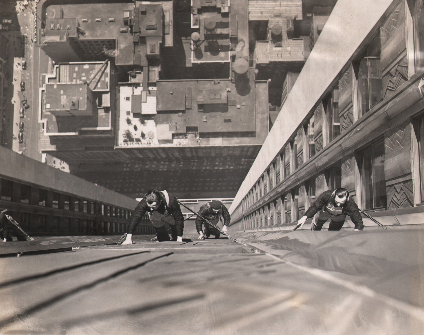 16. Wide World Photos, Human Flies as Window Cleaners, 1938. Downward-looking view of three men suspended against the building facade with the city visible far below and behind them.