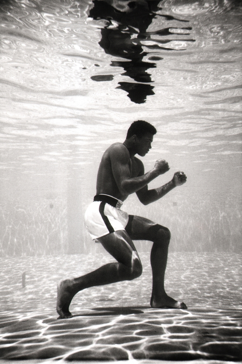 Flip Schulke, Ali Underwater, 1961. Subject holds a boxing pose, pictured in profile at the bottom of a swimming pool.