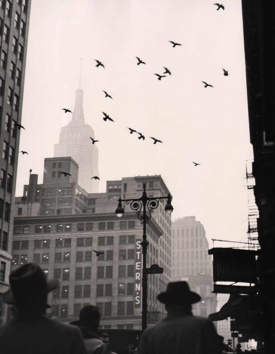 """39. Benn Mitchell, 6th Avenue, NYC, 1949. Vertical street view featuring men in hats in the foreground, a building marked """"Stein's"""" and flying birds in the midground, and a fog-obscured Empire State Building in the left background."""