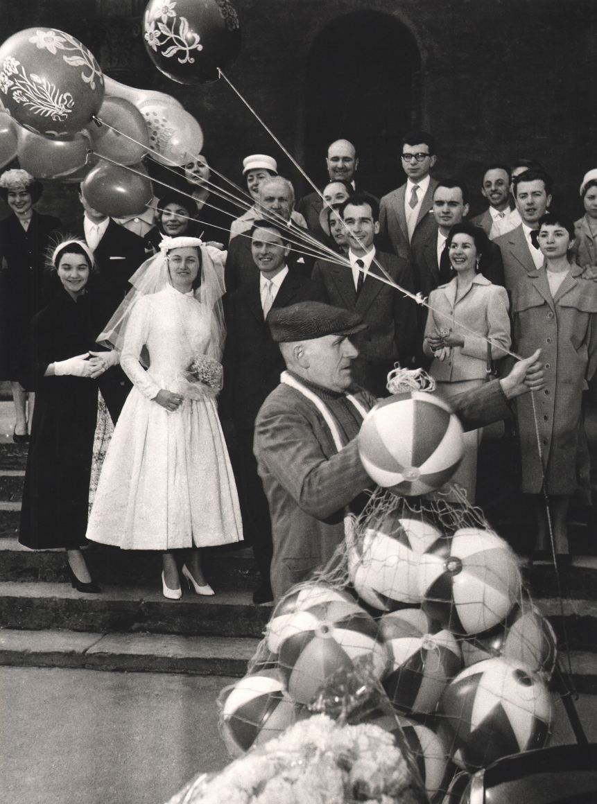 Nino Migliori, People of Emilia, 1952. A group poses for a wedding portrait as a balloon vendor walks through the foreground.