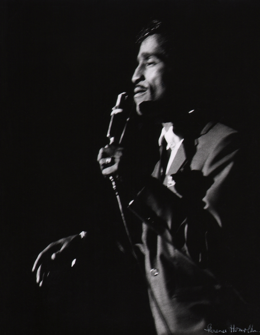 Florence Homolka, Sammy Davis, Jr., c. 1960. Subject is blurred with motion, facing left and holding a microphone on a dark stage.